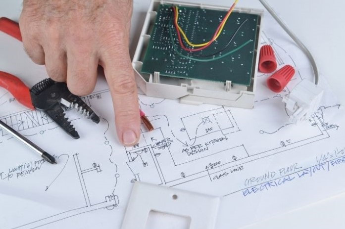 Picture of a electrical handyman services repair provider pointing at electrical drawings where electrical tools are sitting.