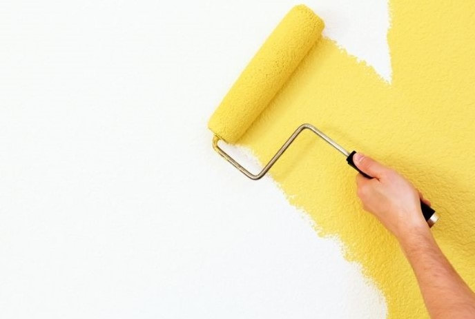 Picture of a painter rolling a paint brush on a wall with yellow paint.