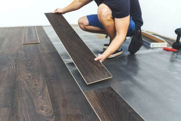 Picture of Handyman Services laying down brown laminate flooring.