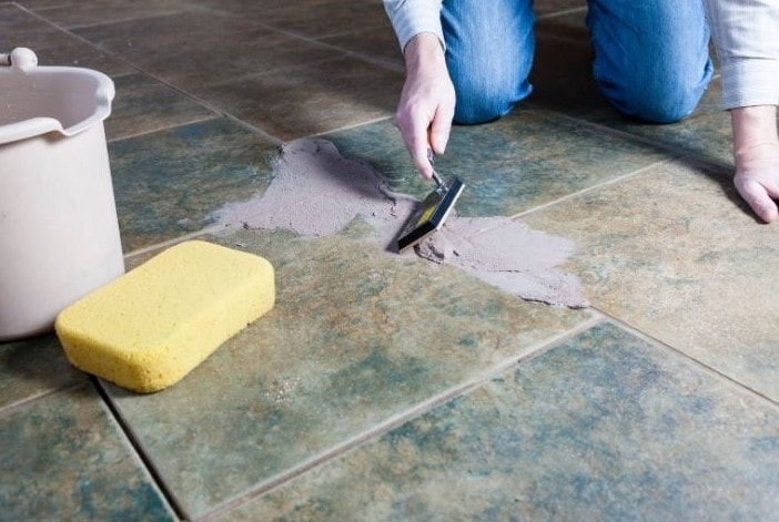 Tile Installation and  repair - Handyman working to spread mortar to lay tiles on the floor using a grouting and tile tool.